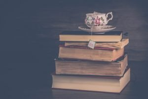 A stack of books with a cup of tea sitting ontop